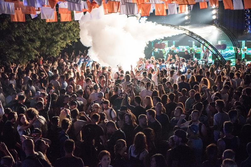 People clubbing and having fun. BONTIDA, ROMANIA - JULY 20, 2018: Crowd of people dancing and clubbing at Electric Castle festival during a Dj Heion concert royalty free stock images