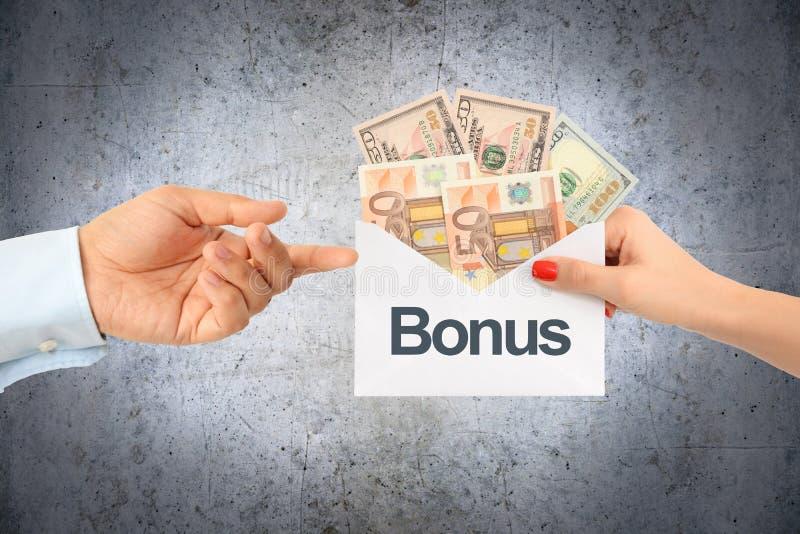 Bonusbetaling voor salaris of verkoopconcept met onderneemster die aan een zakenman een envelop met geld overhandigen royalty-vrije stock afbeeldingen
