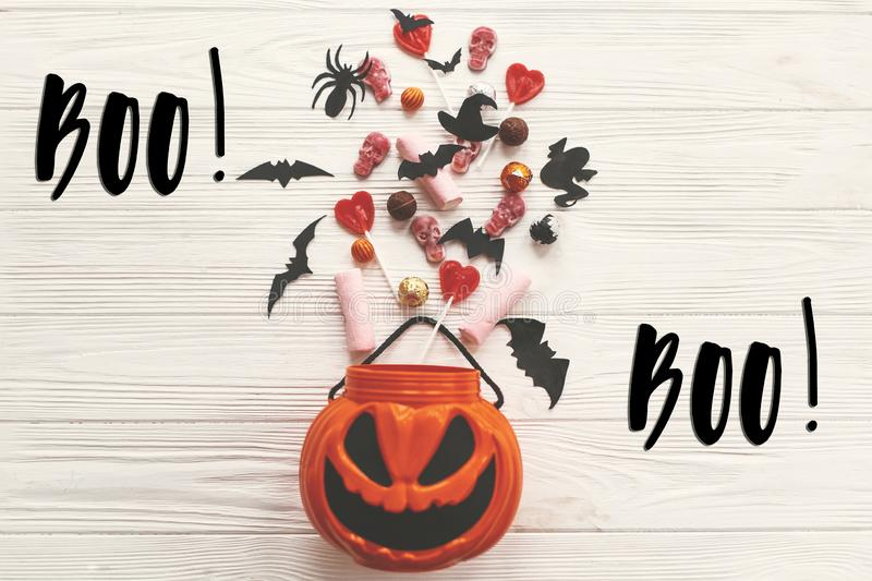 Boo! text sign. Happy Halloween. Jack o Lantern bucket with holiday candy, bats, spiders, skulls on white rustic wooden. Background. Season`s greeting card stock photography