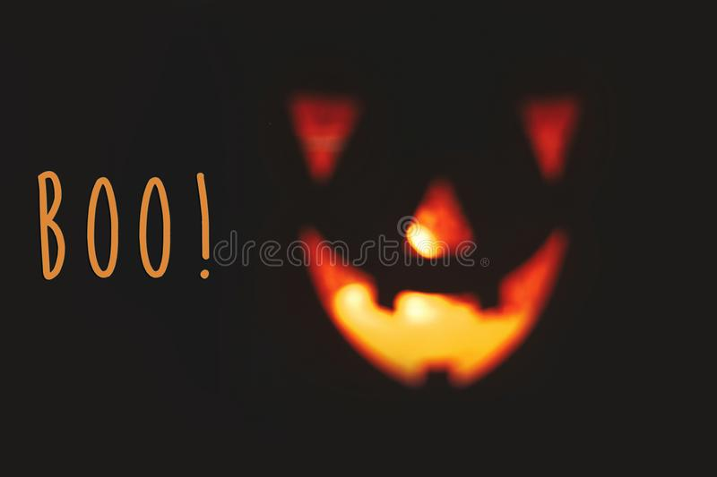 Boo! text, spooky sign. Happy Halloween. Blurred Pumpkin with sc. Ary glowing face on black background isolated. Jack o lantern glowing pumpkin in dark. Season`s royalty free stock image