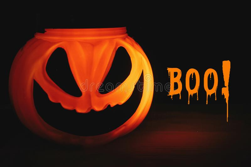 Boo! text, spooky sign. Happy Halloween. Pumpkin with scary glow. Ing face on black background isolated. Jack o lantern glowing pumpkin in dark. Season`s stock photos
