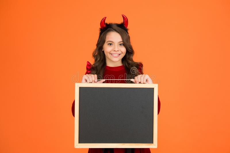 Boo to you from our crew. Little girl cute horns Halloween advertisement. Child imp hold blackboard. Halloween party. Halloween costumes designed after royalty free stock photos