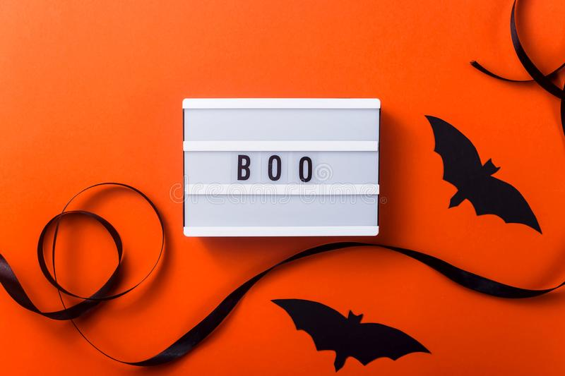Black halloween characters and accessories on a bright orange background. Boo is written on a white panel among accessories for a Halloween party of a black stock photography