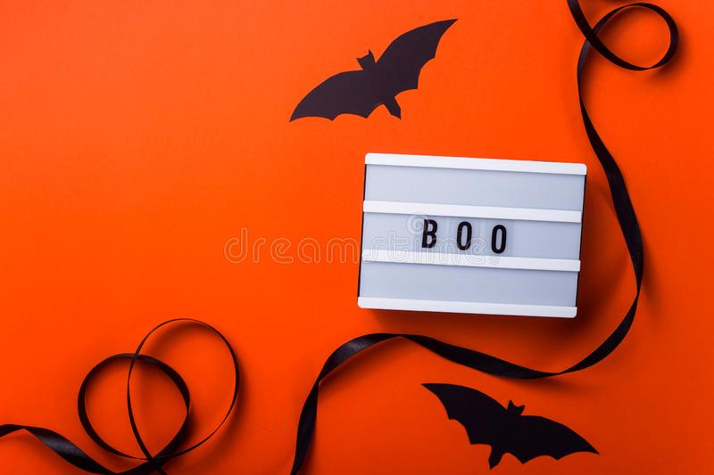 Black halloween characters and accessories on a bright orange background. Boo is written on a white panel among accessories for a Halloween party of a black royalty free stock images