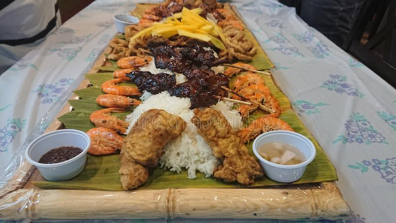Boodle Fight Filipino traditional food preparation based on military practice of eating. royalty free stock photography