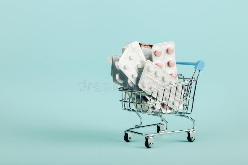 Boodschappenwagentje dat met pillen op een blauwe achtergrond wordt geladen Het concept geneeskunde en de verkoop van drugs De ru royalty-vrije stock foto's