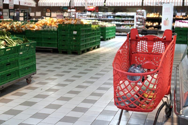 boodschappenwagentje in het fruit en de plantaardige afdeling van een supermarkt royalty-vrije stock afbeeldingen