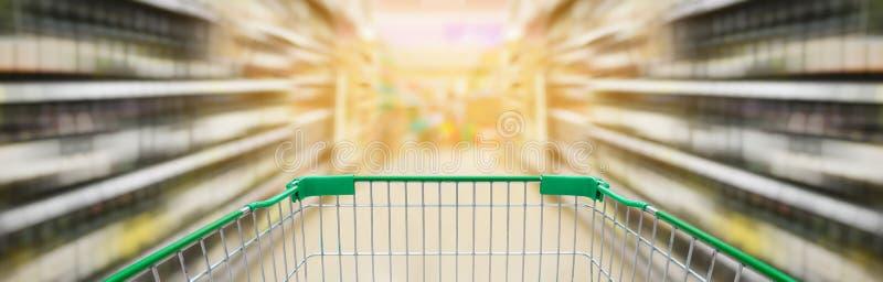 Boodschappenwagentje met de planken van wijnflessen in supermarktdoorgang royalty-vrije stock foto's