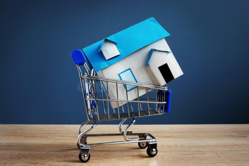 Boodschappenwagentje met model van huis Koop of verkoop bezit stock foto