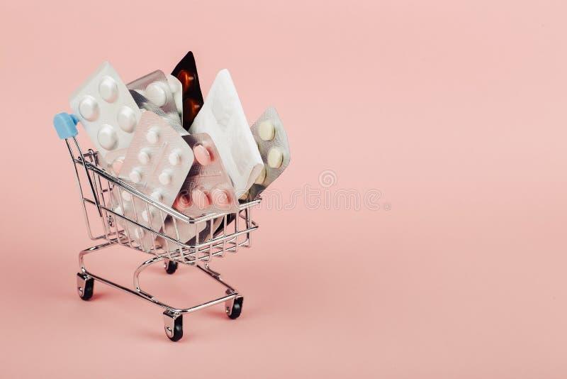 Boodschappenwagentje met pillen op een roze achtergrond wordt geladen die Het concept geneeskunde en de verkoop van drugs De ruim royalty-vrije stock fotografie