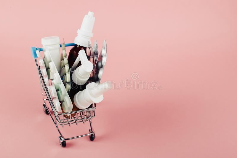 Boodschappenwagentje met pillen op een roze achtergrond wordt geladen die Het concept geneeskunde en de verkoop van drugs De ruim stock afbeeldingen