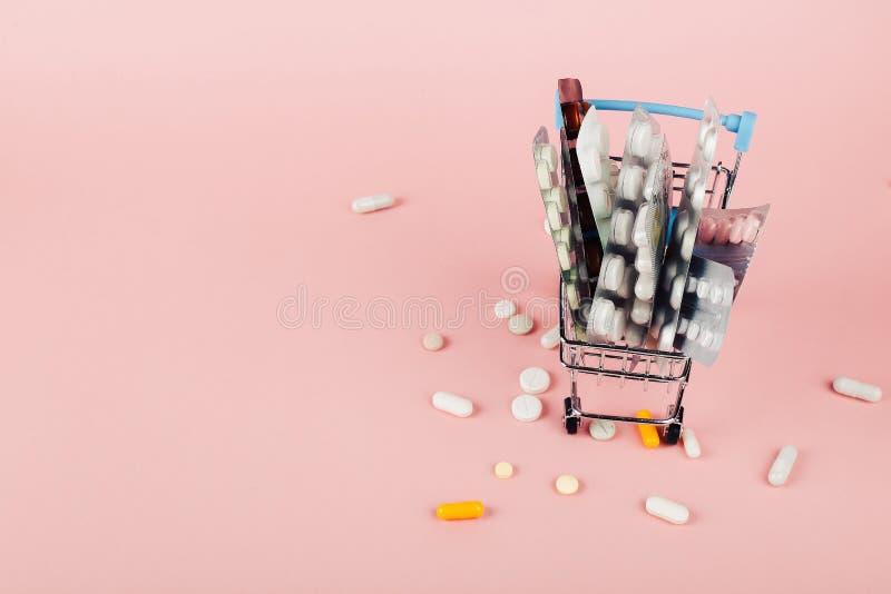 Boodschappenwagentje met pillen op een roze achtergrond wordt geladen die Het concept geneeskunde en de verkoop van drugs De ruim stock fotografie