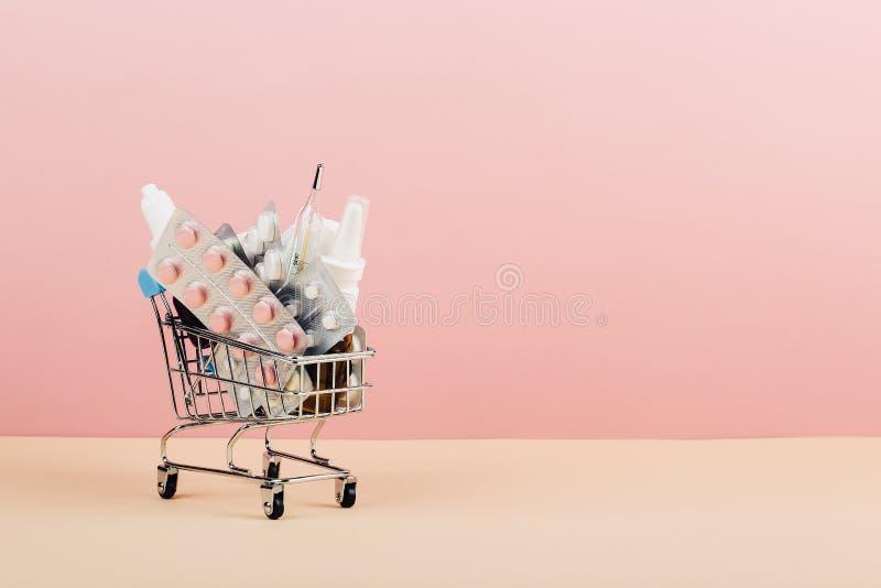 Boodschappenwagentje met pillen op een roze gele achtergrond wordt geladen die Het concept geneeskunde en de verkoop van drugs De stock foto's