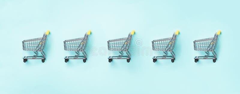 Boodschappenwagentje op blauwe achtergrond Minimalismstijl Creatief ontwerp Hoogste mening met exemplaarruimte Winkelkarretje bij stock foto's