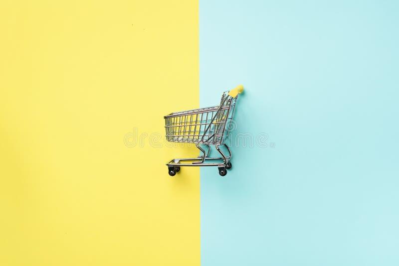 Boodschappenwagentje op blauwe en gele achtergrond Minimalismstijl Creatief ontwerp Hoogste mening met exemplaarruimte Winkelkarr royalty-vrije stock foto
