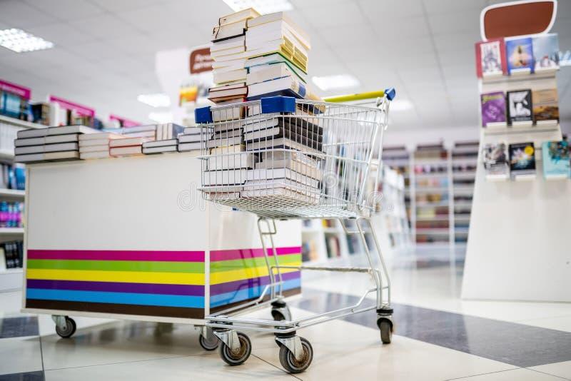 Boodschappenwagentje volledige boeken in boekhandelwinkel dichtbij de planken met boeken royalty-vrije stock afbeelding