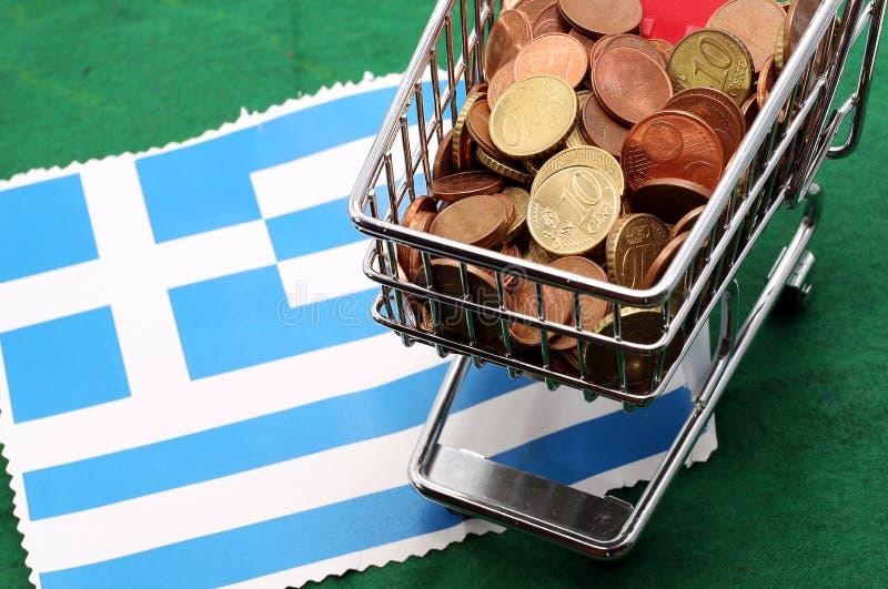 Boodschappenwagentjehoogtepunt van euro geld over Vlag van Griekenland stock afbeelding