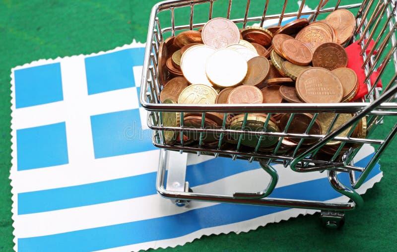 Boodschappenwagentjehoogtepunt van euro over Vlag van Griekenland royalty-vrije stock afbeeldingen