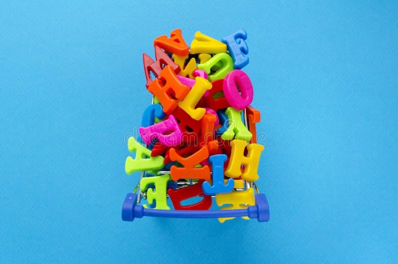 Boodschappenwagentjehoogtepunt van stuk speelgoed gekleurde brieven op blauwe achtergrond royalty-vrije stock afbeelding