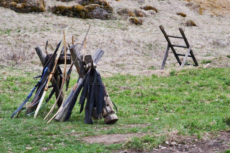 Boog en pijlen op de achtergrond van de oude houten treden, het groene gras en mos, het droge gras en de aarde royalty-vrije stock foto