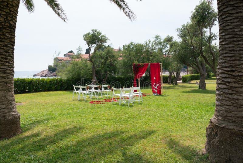 Boog en stoelen met verse bloemen in rode tonen voor de huwelijksceremonie wordt verfraaid op het groene gazon dat stock afbeelding