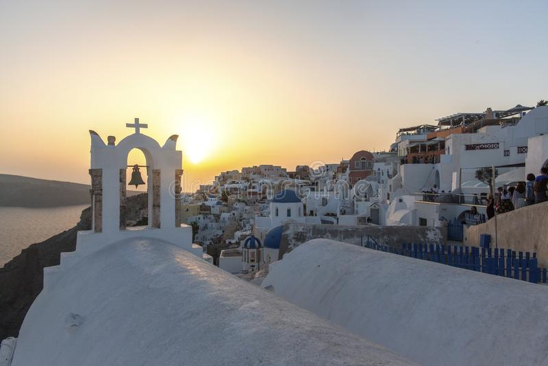 Boog met een klok, witte huizen en een kerk met blauwe koepels in Oia of Ia bij gouden zonsondergang, eiland Santorini, Griekenla stock foto's