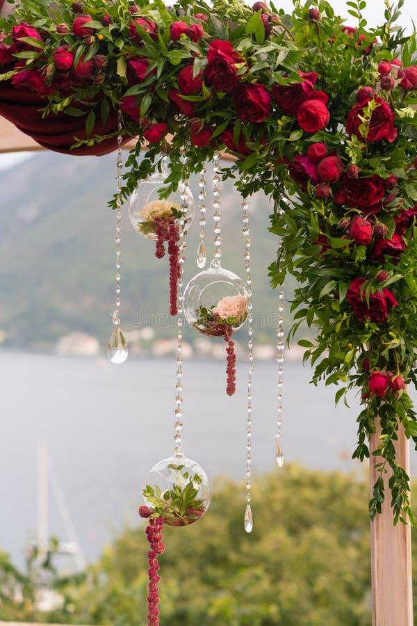 Boog met verse bloemen in donkerrode tonen voor de huwelijksceremonie die wordt verfraaid stock afbeeldingen