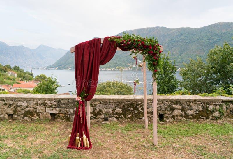 Boog met verse bloemen in donkerrode tonen voor de huwelijksceremonie die wordt verfraaid royalty-vrije stock foto's