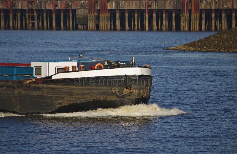 Boog van binnenlands schip bij volledige snelheid met witte schuimende boeggolf en pijler op de achtergrond royalty-vrije stock foto's