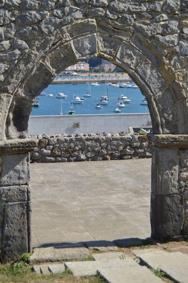 Boog van de mooie doen ineenstorten muur van de kerk van San Pedro die de vissershaven op Paseo Maritimo binnen overzien stock afbeelding