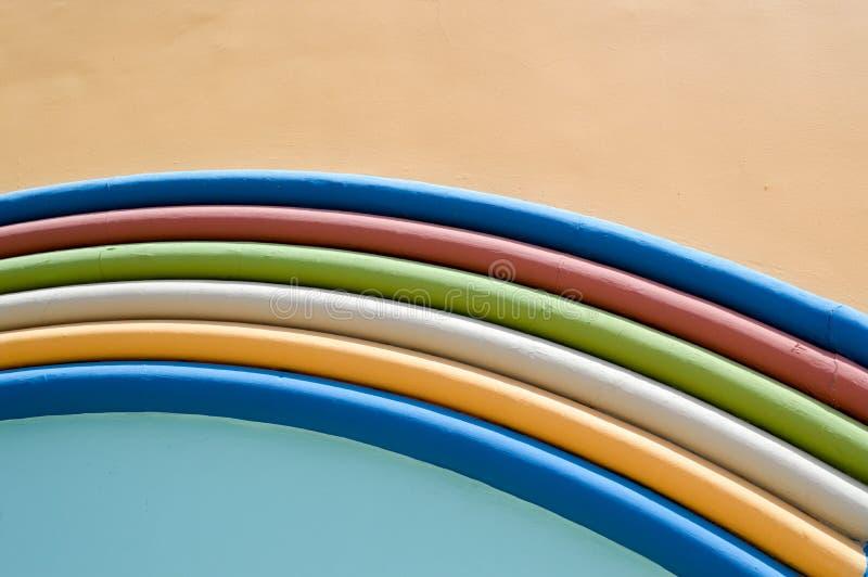 Boog van de textuur de abstracte kleurrijke heldere bont feestelijke regenboog van decoratieve gipspleistersteen op een blauwe en stock foto's