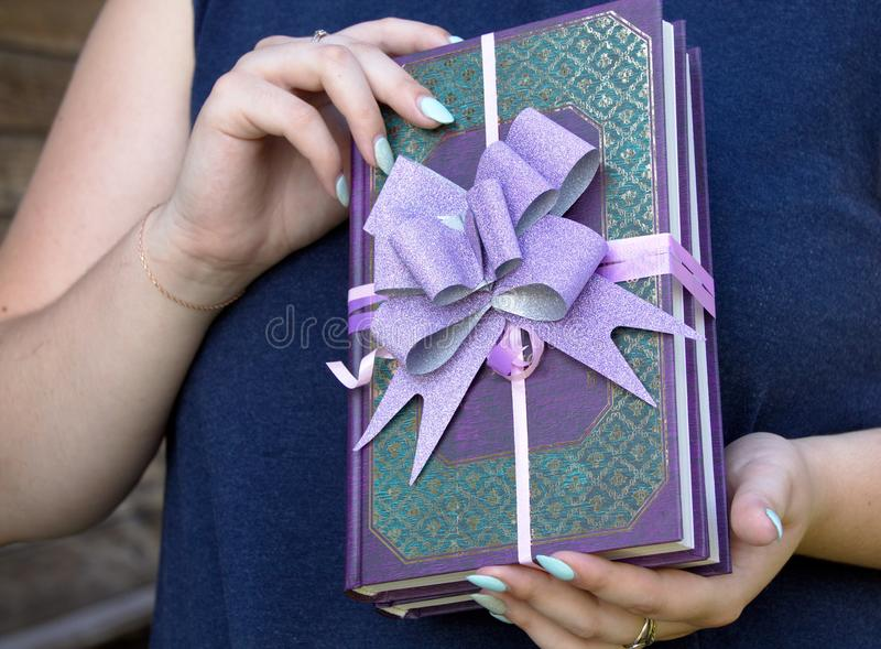 The book as a gift holds women`s hands beautiful design with a bow. On the background of the chest royalty free stock photos