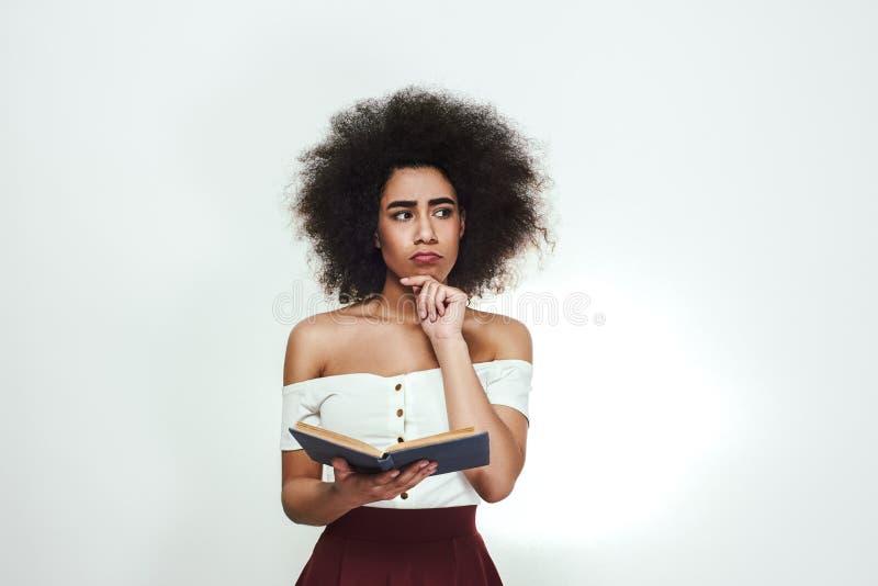 book avläsning Den fundersamma unga afro amerikanska kvinnan med lockigt hår är läseboken som trycker på hennes haka och tänka arkivbild