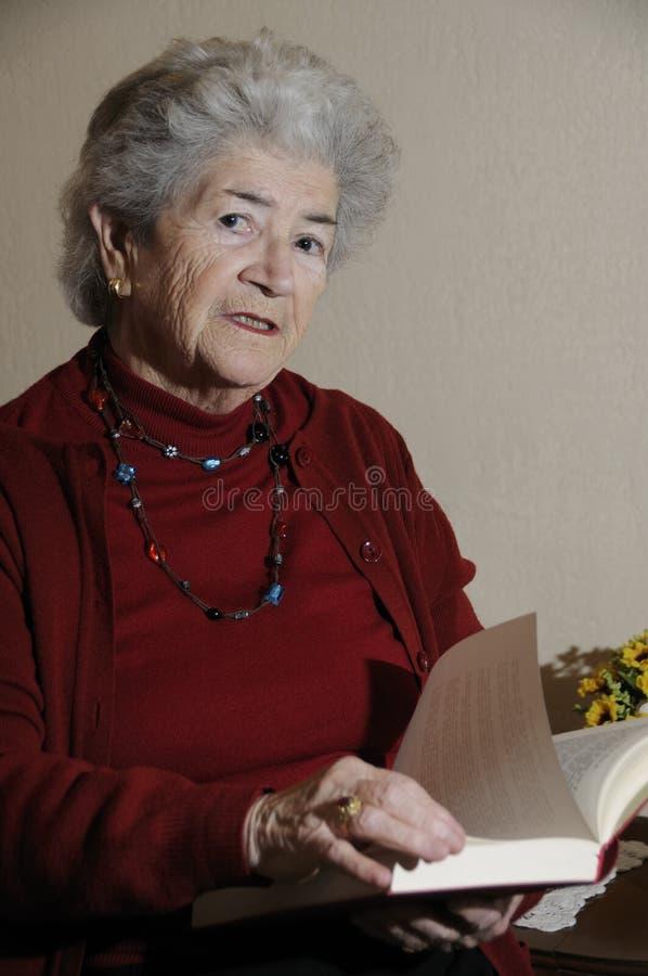 book avläsningspensionärkvinnan royaltyfria bilder