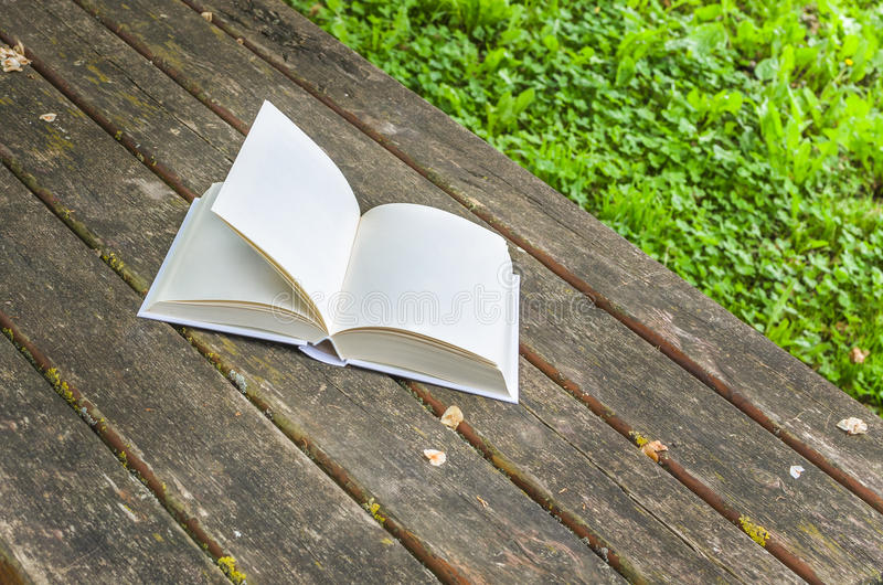 Book with Blank Pages on a Wooden Table. Book with blank pages lying open on a wooden table in a park stock photos
