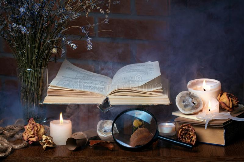Book, candles, smoke. Mysterious dark still life. Dried flowers, rose petals. Fairy atmosphere stock image