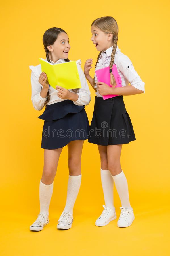Book Club. cheerful classmates with workbook. little girls in school uniform. back to school. reading story. childrens. Literature. information. dictionary stock images