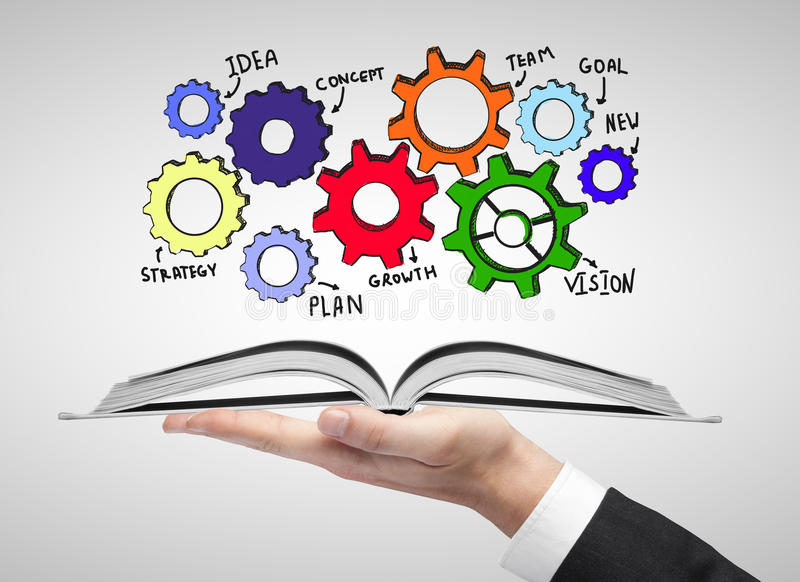 Book with cogwheel sketch. Hand holding open book with abstract cogwheel sketch stock image