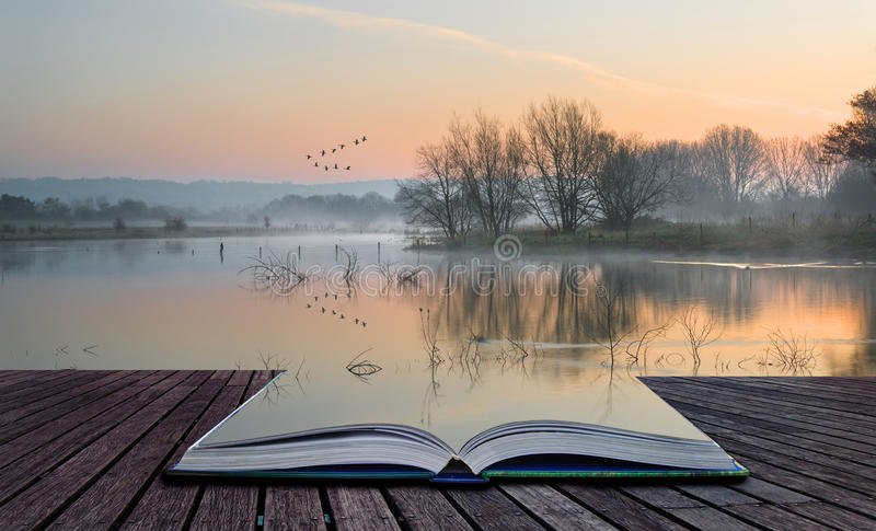 Book concept Landscape of lake in mist with sun glow at sunrise stock photo