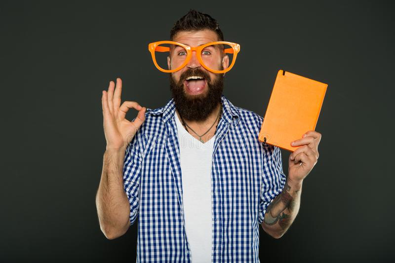 Book cover copy space. Hipster bearded man wear funny eyeglasses hold notepad or book. Bright up your day. Read this stock image