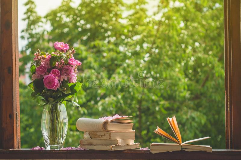 Book, croissant, cup of tea and roses on a wooden window. Read books. Romantic concept stock image