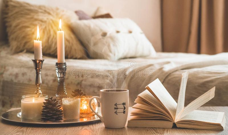 Book, cup of coffee and many candles on the home background.  Home and home decor. Candles flame stock images