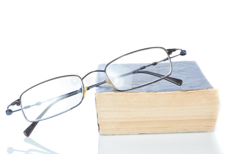 Book is a dictionary and glasses. The book is a dictionary and glasses on a white background royalty free stock photo