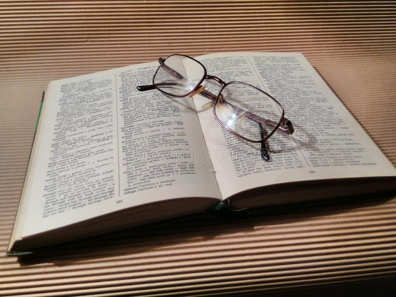 Book. Dictionary, glasses, studying, school, home stock images