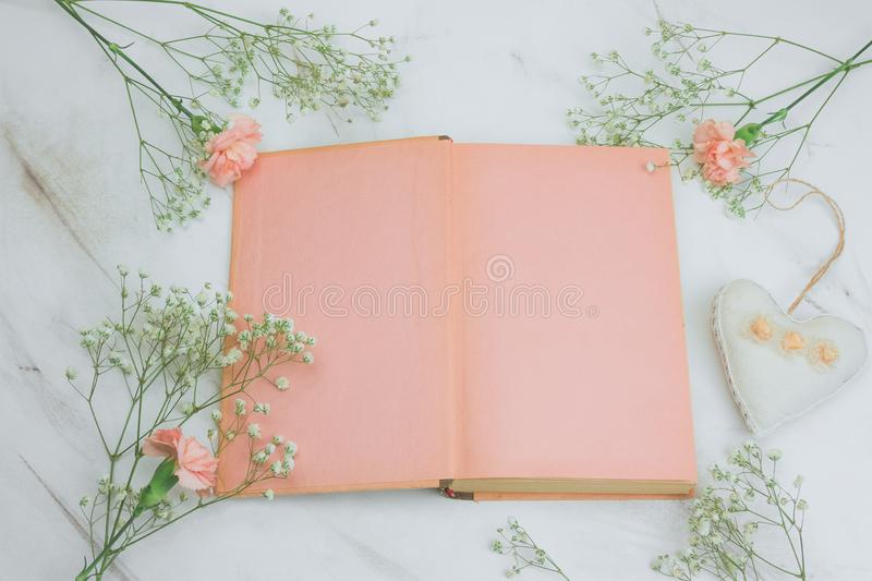 Book with empty sheets and flowers on a marble background. Top view vintage book with empty sheets and flowers on a marble background stock photos
