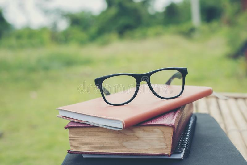 Book and eye glasses for read and write over blurred nature outdoor background. royalty free stock image