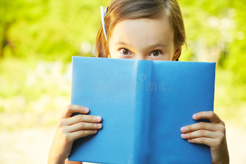 Book and eyes. Girl looks out from behind a blue book stock photo