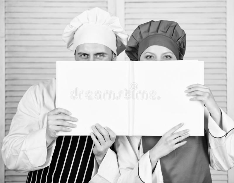 Book family recipes. Cooking guide. According to recipe. Manand woman chef hide faces behind open book. Guy and girl royalty free stock images