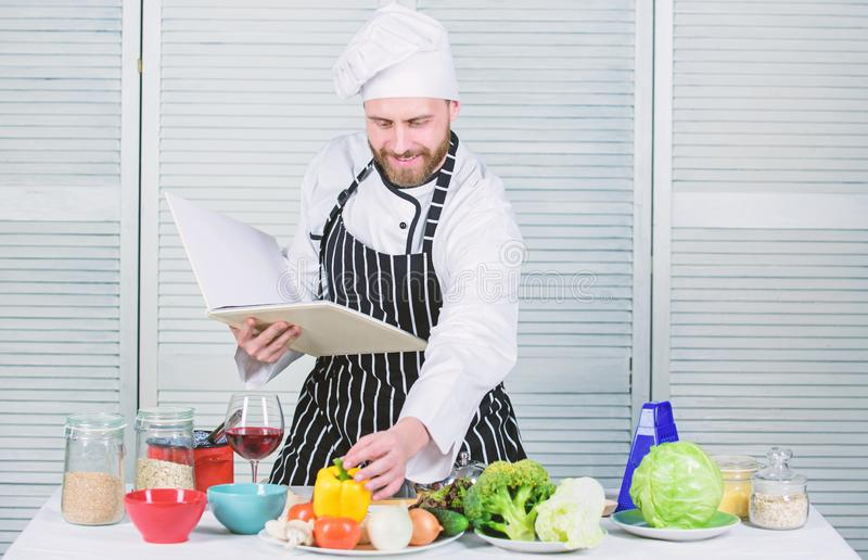 Book family recipes. Ultimate cooking guide for beginners. According to recipe. Man bearded chef cooking food. Guy read. Book recipes. Culinary arts concept stock photography