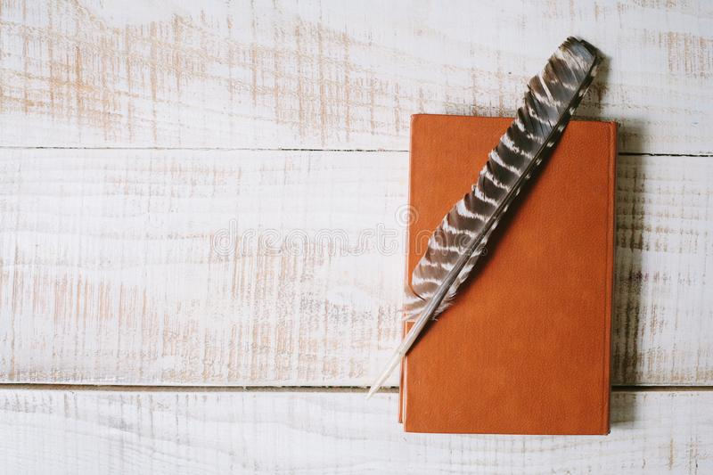 Book and feather lie on a wooden table. top view. layflat royalty free stock image